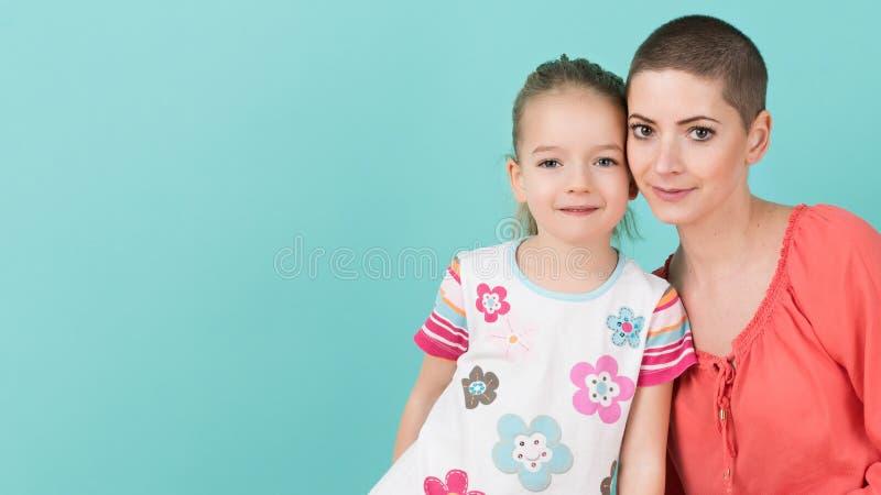 Fille préscolaire mignonne d'âge avec sa mère, jeune cancéreux dans la remise Appui de cancéreux et de famille images libres de droits