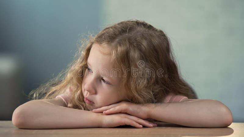 Fille préscolaire s'asseyant à la table et allant pleurer, abus d'enfants, solitude photo libre de droits