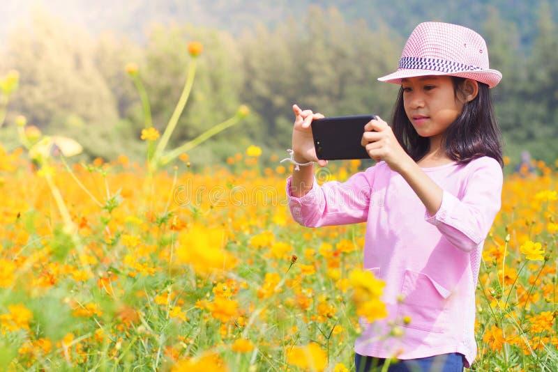 Fille prenant des téléphones portables de photo dans le domaine de fleurs image libre de droits