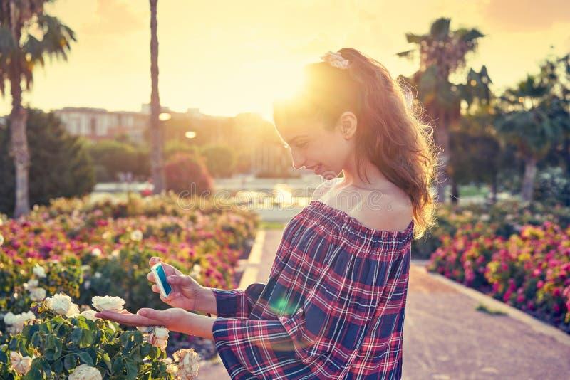 Fille prenant la photo de smartphone à la fleur rose image stock