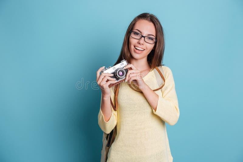 Fille prenant la photo utilisant le photocamera au-dessus du fond bleu photographie stock libre de droits