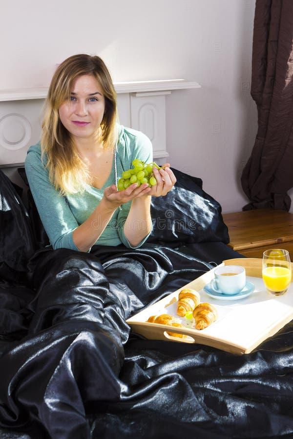 Fille prenant le petit déjeuner dans le lit photos stock