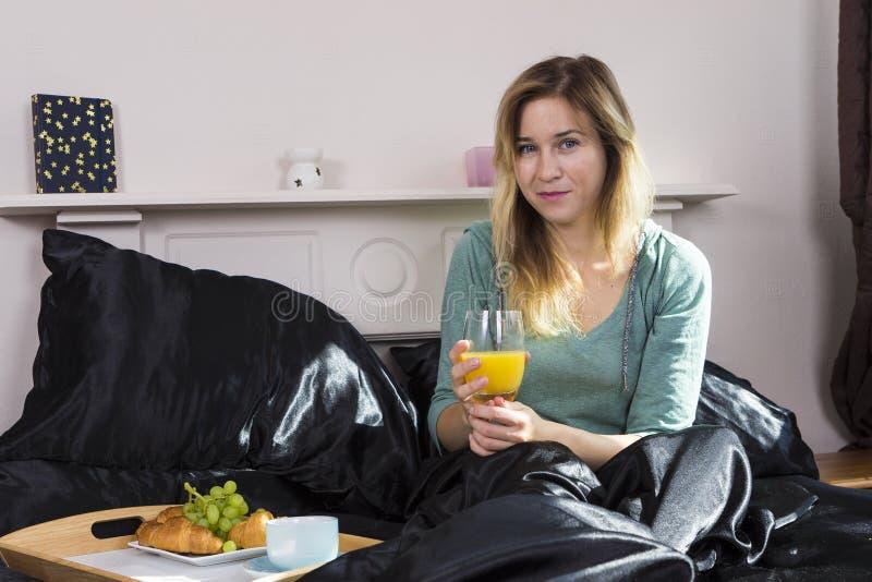 Fille prenant le petit déjeuner dans le lit photographie stock
