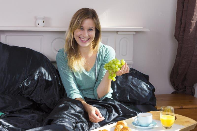 Fille prenant le petit déjeuner dans le lit photographie stock libre de droits