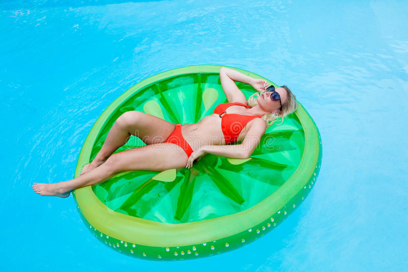 Fille prenant un bain de soleil sur gonflable dans la piscine images libres de droits