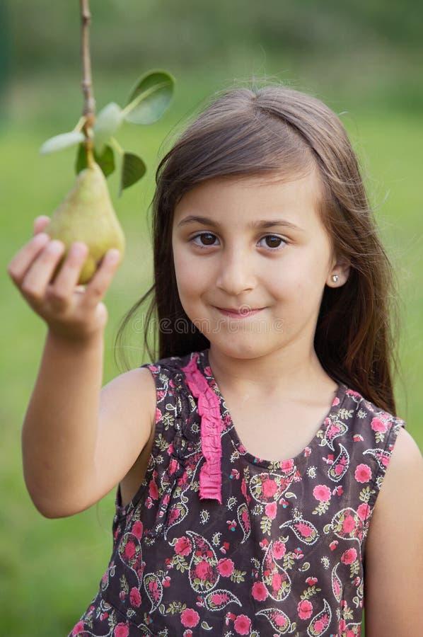 Fille prenant une poire photo libre de droits