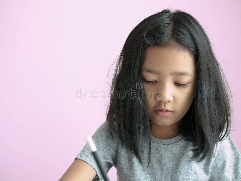 Fille principale malpropre écrivant un livre avec l'espace rose de fond et de copie photos libres de droits