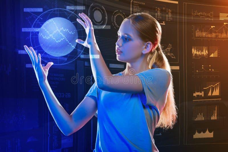 Fille progressive tenant un hologramme et le regardant photos stock