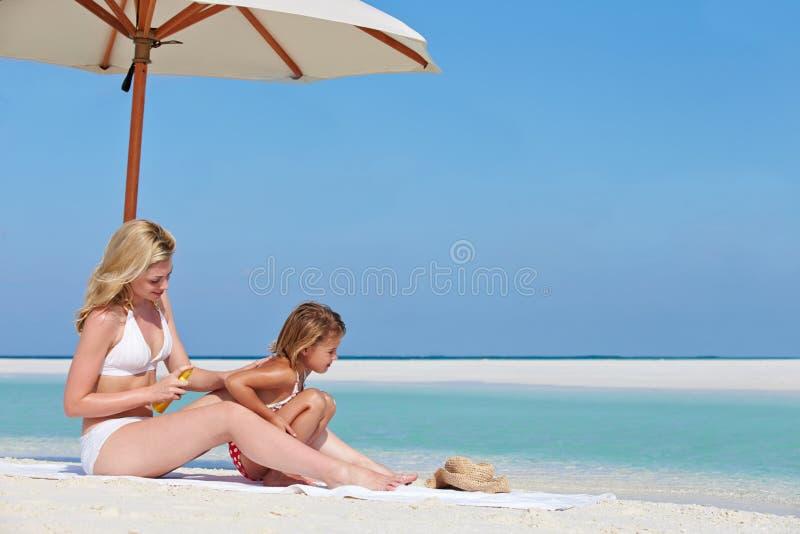 Fille protectrice de mère avec la lotion de Sun des vacances de plage images stock