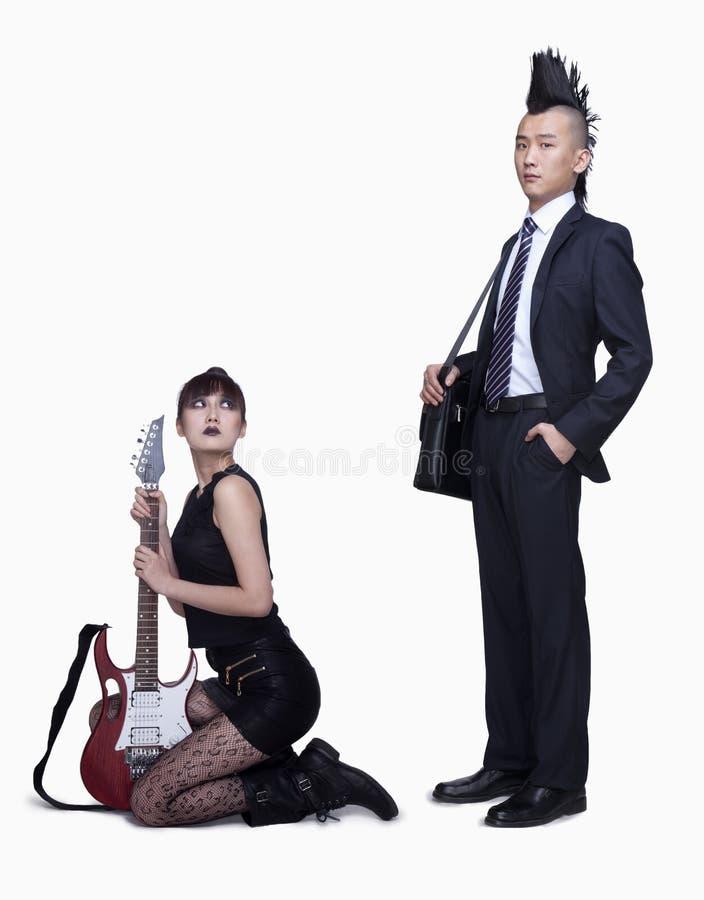 Fille punk avec la guitare et homme d'affaires punk sérieux, tir de studio photographie stock