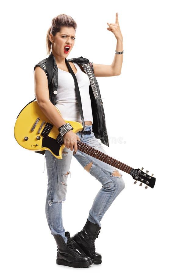 Fille punk avec une guitare électrique faisant le geste de main de roche photos libres de droits