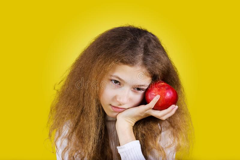 Fille réfléchie avec la pomme rouge près de sa tête photos stock