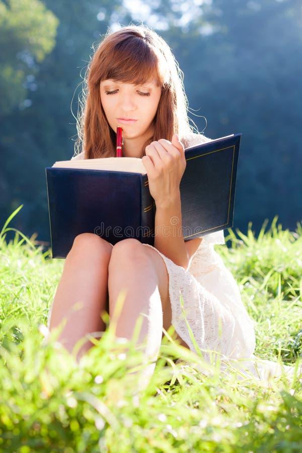 Fille réfléchie avec un livre sur la nature photographie stock libre de droits