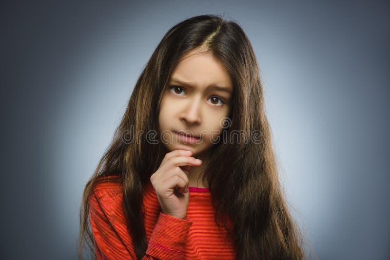 Fille réfléchie de plan rapproché avec la main à la tête d'isolement sur le gris photo libre de droits