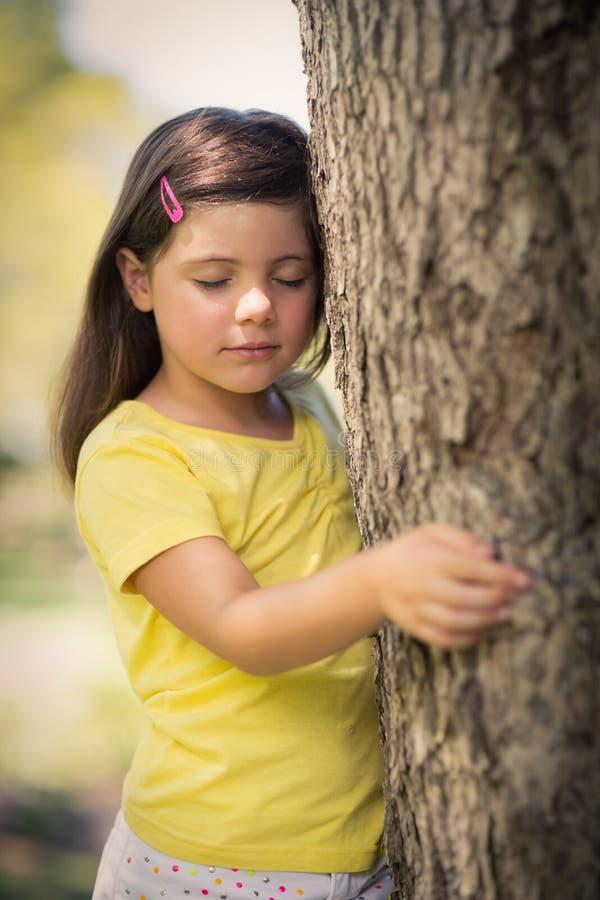 Fille réfléchie se penchant sur le tronc d'arbre photographie stock