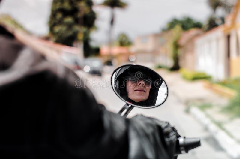 Fille réfléchie sur le miroir de motocyclette photo stock