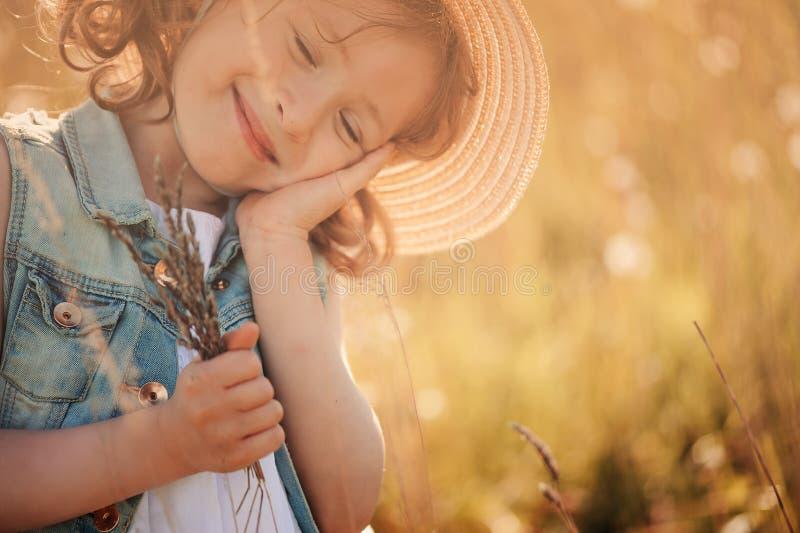 Fille rêvante heureuse d'enfant tenant le bouquet en été photos stock