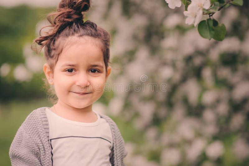 Fille rêveuse heureuse mignonne d'enfant d'enfant en bas âge marchant dans le jardin de floraison de ressort, célébrant Pâques ex image libre de droits
