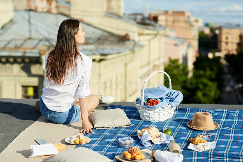 Fille rêveuse prenant le déjeuner sur le toit photographie stock