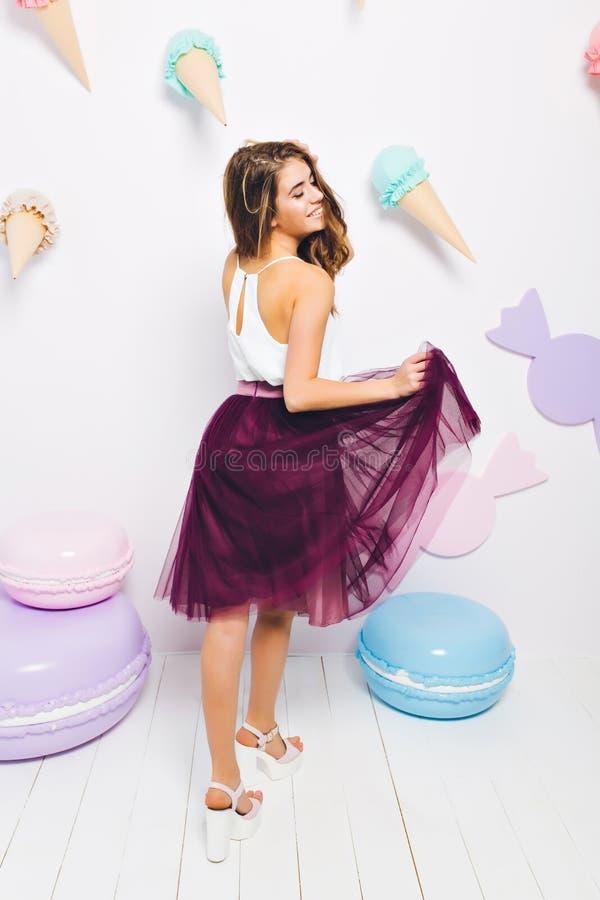 Fille rêveuse riante dans le jeu au dessus du réservoir blanc avec sa jupe luxuriante, se tenant près des macarons colorés de jou images stock
