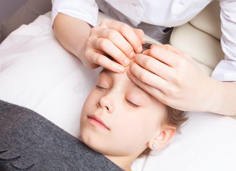 Fille recevant le traitement osteopathic de sa tête photos stock