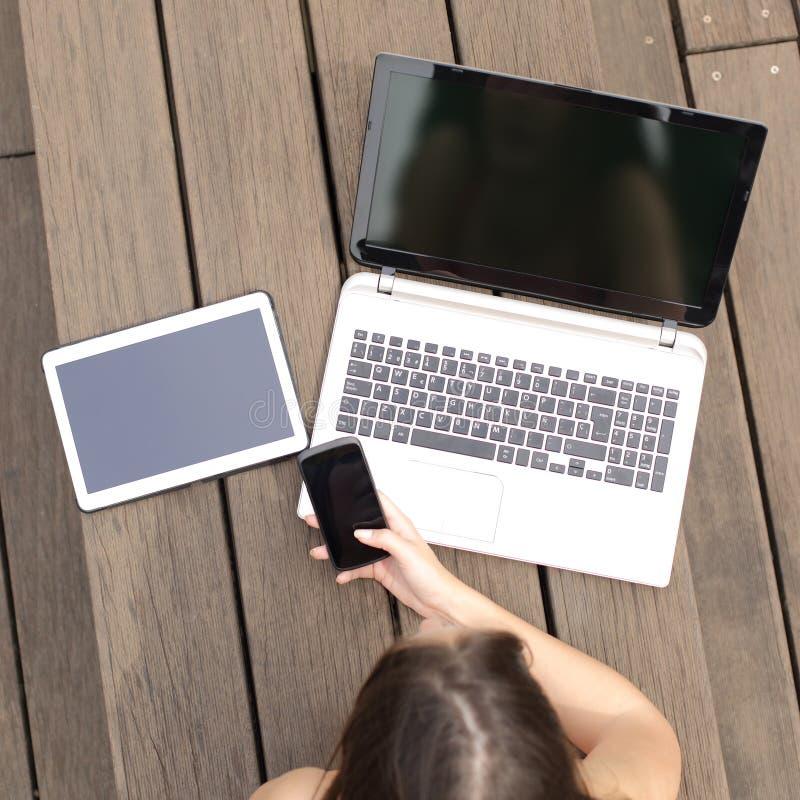 Fille recherchant le travail dans des écrans multiples de dispositifs photos libres de droits