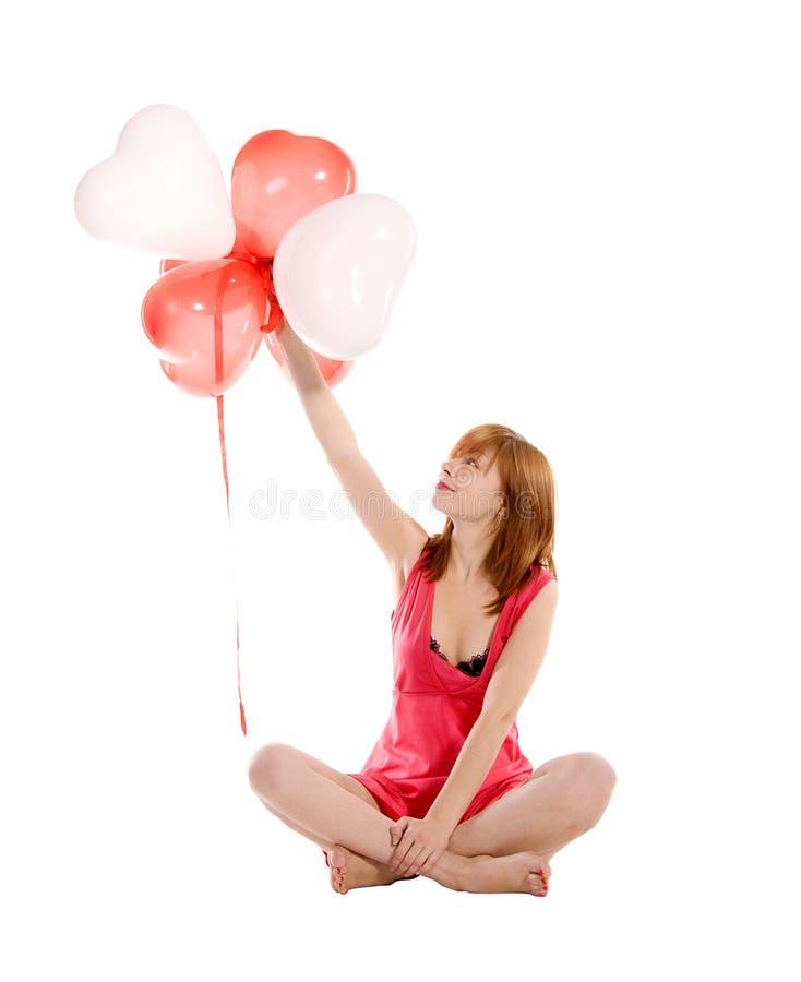 Fille Red-haired dans une robe rose avec des ballons photos libres de droits
