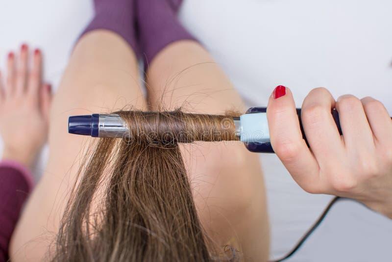 Fille redressant ses cheveux dans le lit photographie stock