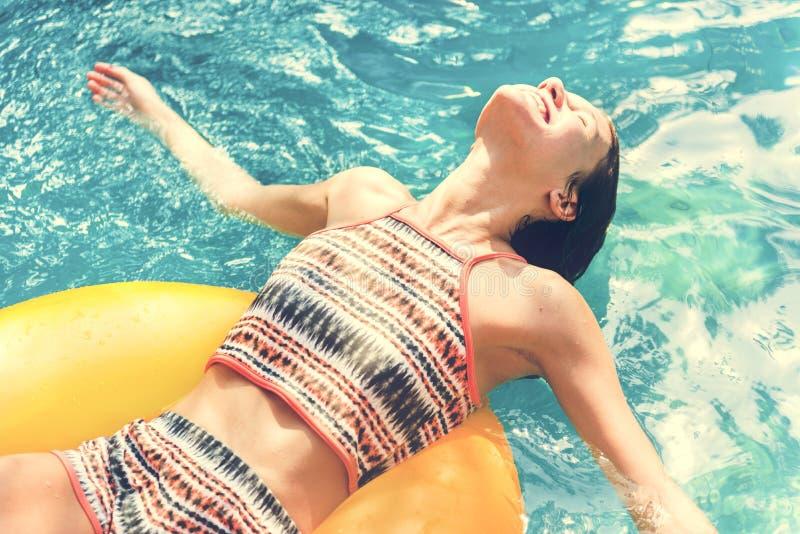 Fille refroidissant dans une piscine photo libre de droits