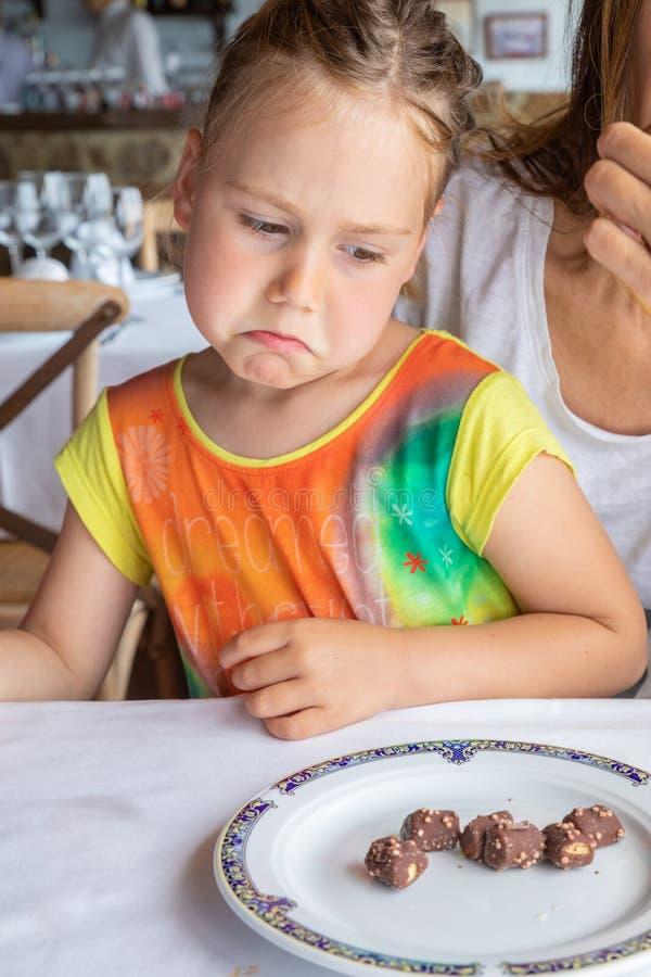 Fille regardant avec l'expression contrariée des chocolats sur son pla photo stock
