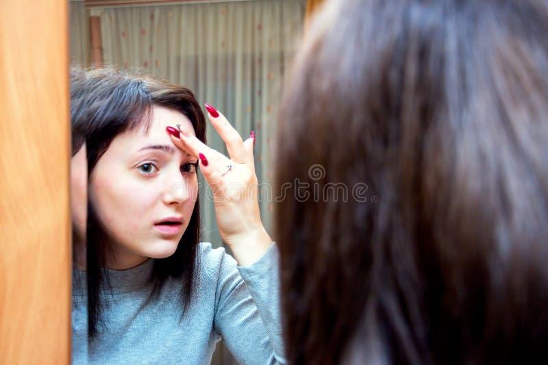 Fille regardant dans le miroir photos stock