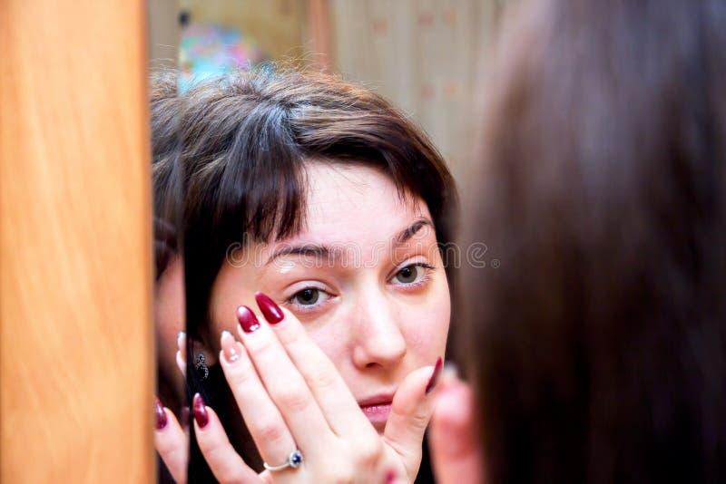 Fille regardant dans le miroir photographie stock libre de droits