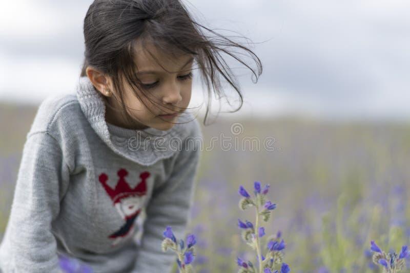 Fille regardant des fleurs image stock
