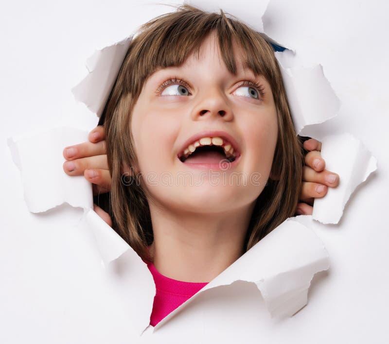 Fille regardant hors d'un trou dans un papier image libre de droits
