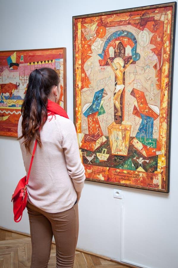 Fille regardant la peinture de Fulla, Slovaquie photographie stock libre de droits
