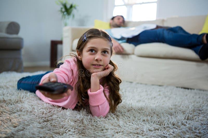 Fille regardant la TV se trouver sur la couverture dans le salon photographie stock libre de droits