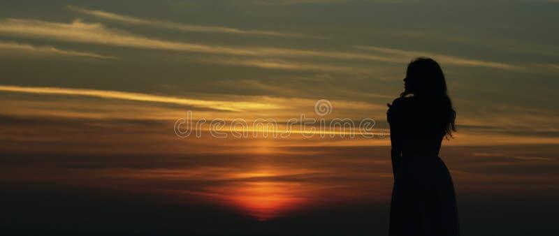 Fille regardant le coucher du soleil photo stock