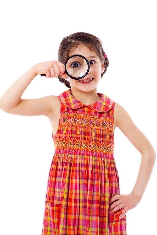 Fille regardant par une loupe photos stock