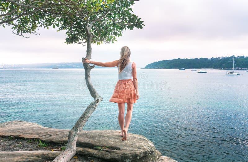 Fille regardant pour voir se tenir dessus au vent solitaire d'arbre dans ses cheveux images stock