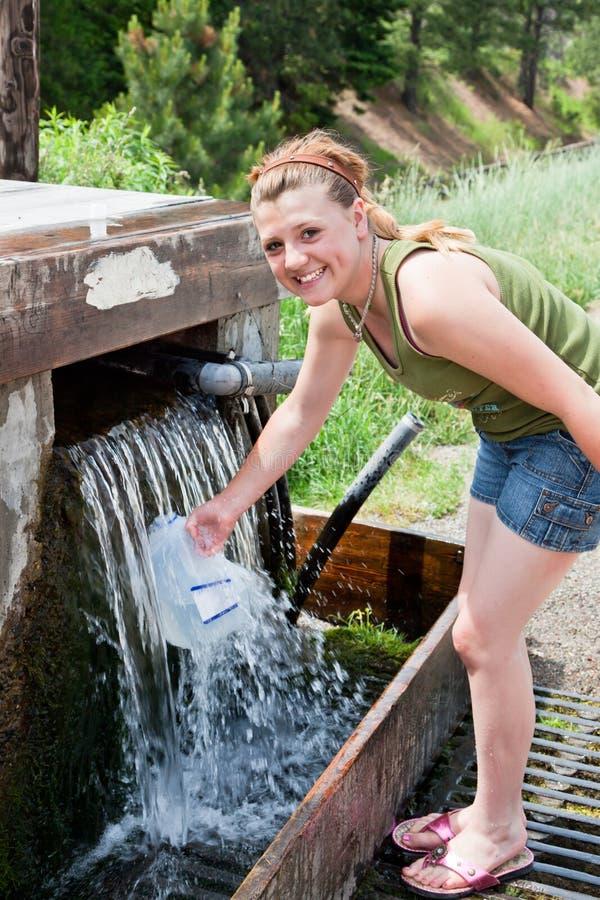 Fille remplissant une cruche d'eau photo libre de droits