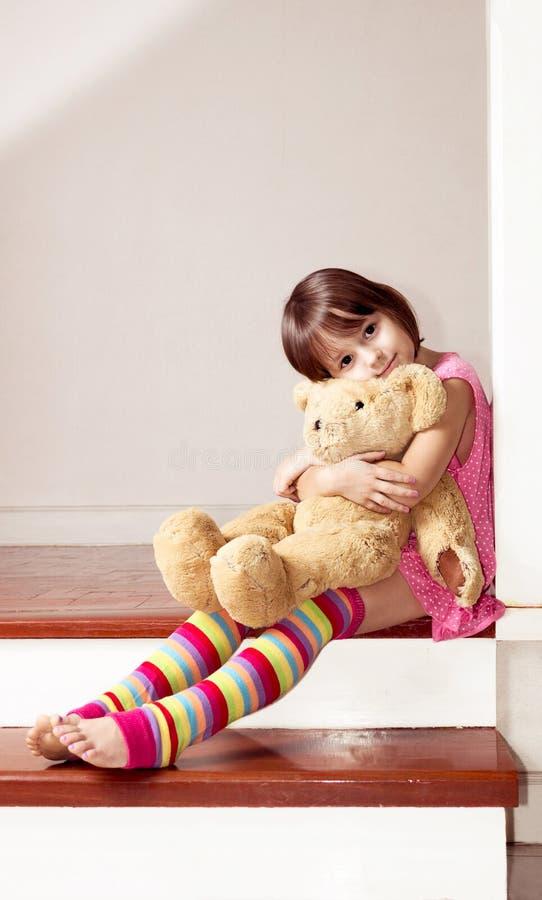 Fille reposant et tenant l'ours de nounours photographie stock libre de droits