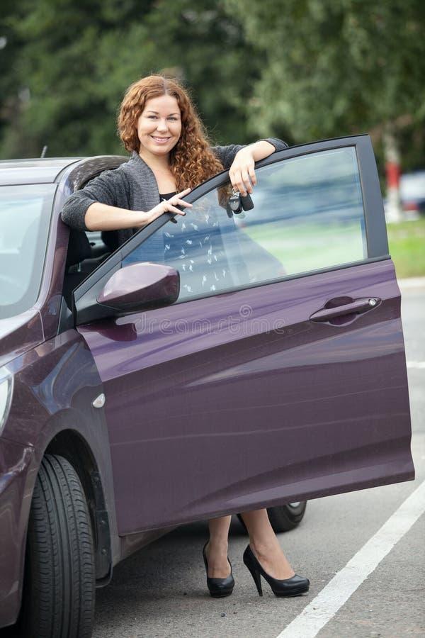 Fille riante avec les cheveux bouclés se tenant près de votre nouvelle voiture images libres de droits
