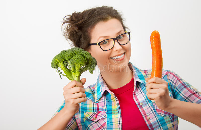 Fille riante avec les verres et le brocoli et la carotte dans les mains images stock