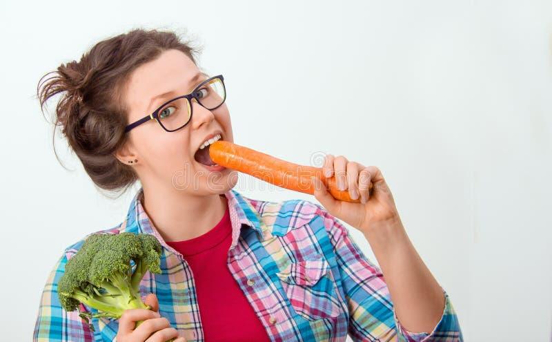Fille riante avec les verres et le brocoli et la carotte dans les mains photographie stock libre de droits