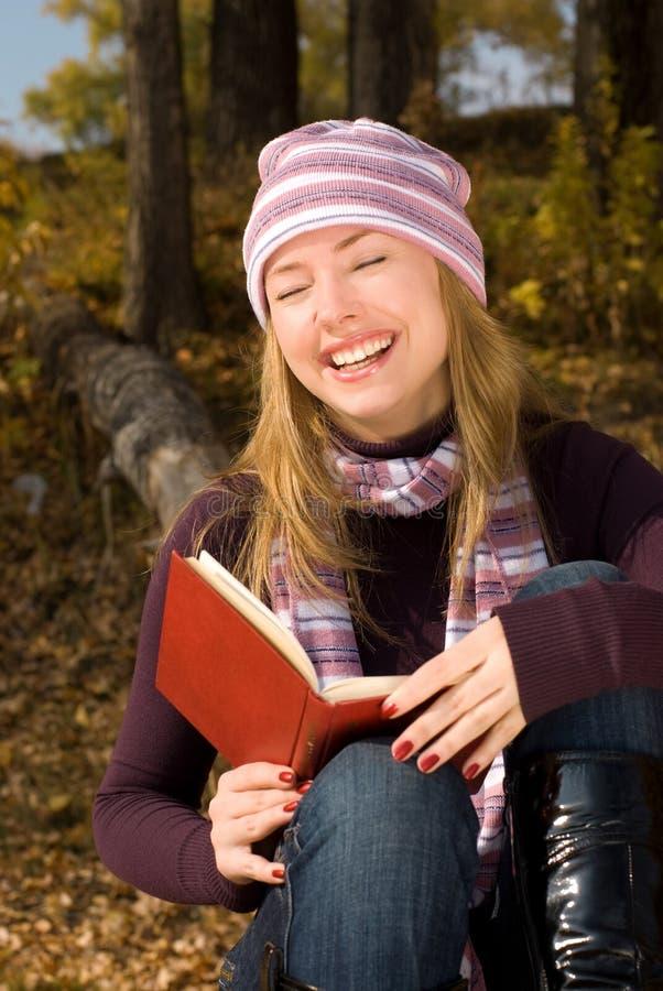 Fille riante avec un livre photos libres de droits