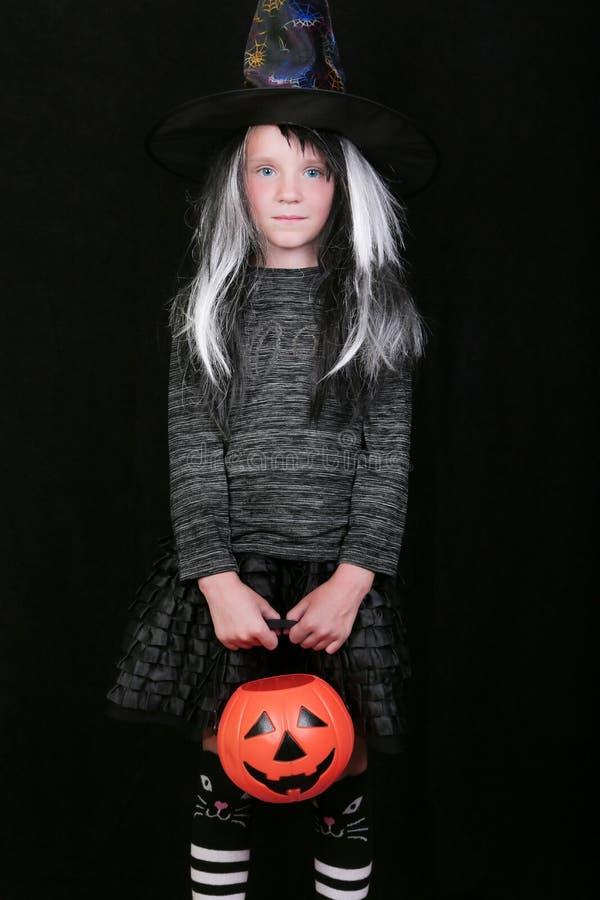 Fille riante heureuse d'enfant dans le costume de sorcière avec le pot de sucrerie de potiron de Halloween sur le fond noir images stock