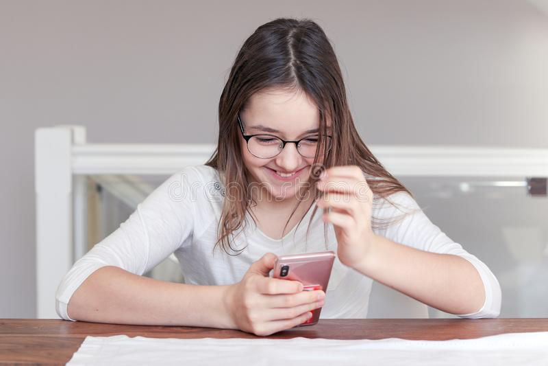 Fille riante heureuse mignonne de tween en verres regardant le smartphone dans des ses mains parlant à l'appel visuel avec le sou images stock