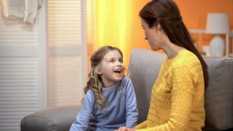 Fille riante heureuse racontant ? maman de sourire des histoires dr?les, relations confiantes images stock