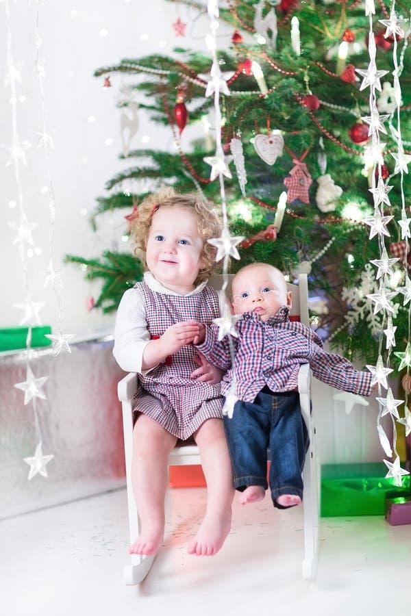 Fille riante mignonne d'enfant en bas âge et son petit frère de bébé sous l'arbre de Noël photo libre de droits