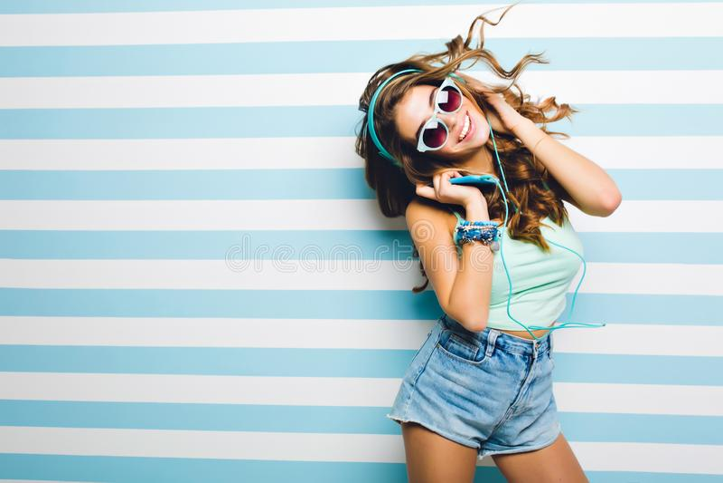 Fille riante mince dans la danse drôle de shorts à la mode de denim tenant de grands écouteurs Jeune femme bronzée attirante deda image libre de droits